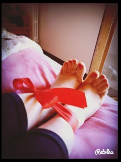 Piedi smaltati di rosso legati